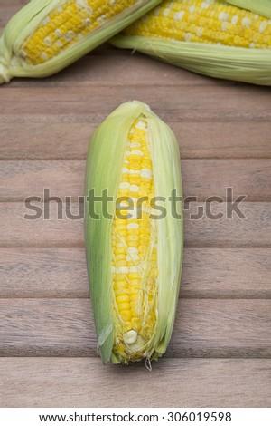 Fresh corn on wooden background - stock photo