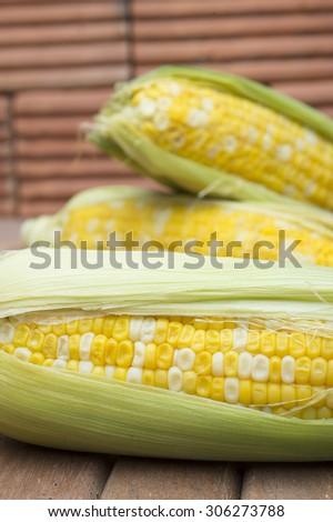 Fresh corn on wooden floor with brick background - stock photo