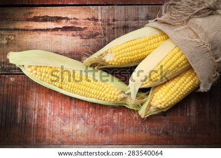 fresh corn on wooden table - stock photo