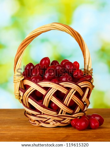 fresh cornel berries in wicker basket on green background close-up