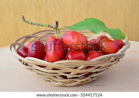 Fresh cornelian cherries in small wicker basket on the table, against wooden background