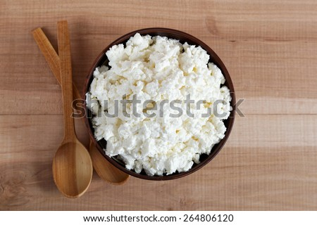 Fresh cottage cheese in a bowl with spoon on a wooden table. - stock photo