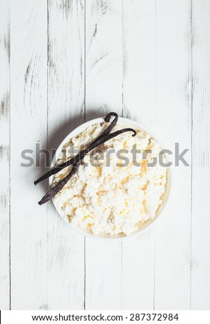 Fresh cottage cheese on the plate and vanilla pods, baking preparations - stock photo
