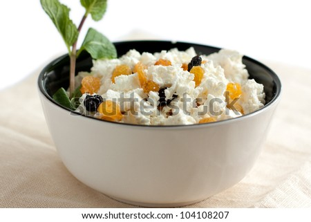 Fresh cottage cheese with yellow and blue raisins in a round white bowl