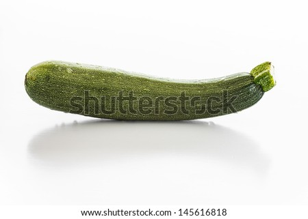 Fresh courgette with water drops over a white background. - stock photo