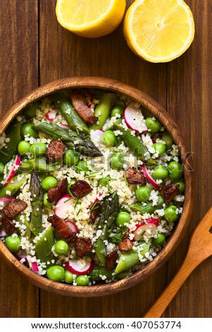 Fresh couscous salad with green asparagus, peas, radish slices, fried bacon pieces and chives, photographed overhead on dark wood with natural light (Selective Focus, Focus in the top of the salad)