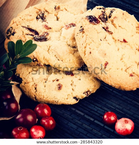 Fresh cowberries with cookies, close up on black mat, instagram style filtered - stock photo