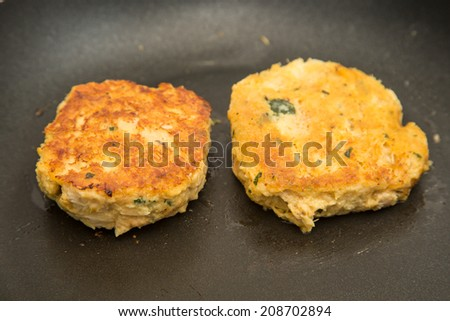 Fresh crab cakes browning in hot oil in a pan - stock photo