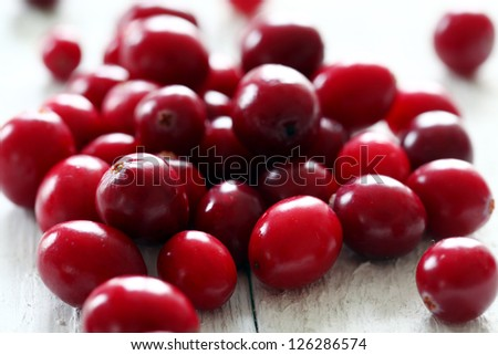 Fresh cranberries on a white wooden surface - stock photo