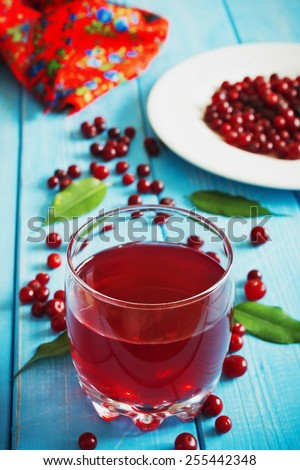 fresh cranberry juice in a glass and fresh cranberries on a blue wooden background.health and diet food - stock photo
