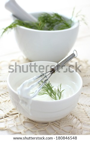 Fresh cream cheese spread in white bowl with dill and corolla - stock photo