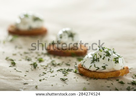 Fresh cream cheese spread with dill on bake rolls - stock photo