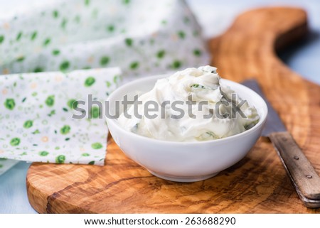 Fresh cream cheese spread with herbs in a bowl, selective focus - stock photo