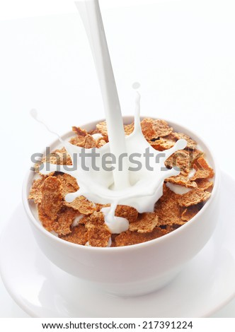 Fresh creamy milk splashing into a bowl of tasty flavored chocolate cereal flakes for a delicious breakfast and energizing start to the morning - stock photo