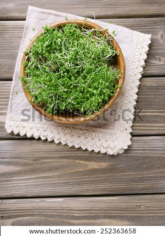 Fresh cress salad in bowl on napkin and wooden planks background - stock photo