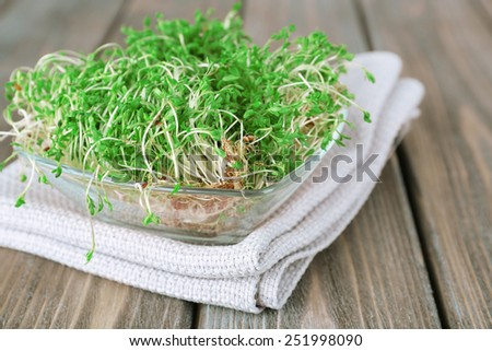 Fresh cress salad in glass bowl with napkin and wooden planks background - stock photo