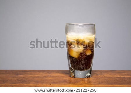 Fresh, crisp, cold cola being poured into a drinking glass. - stock photo