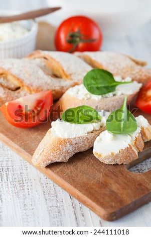 Fresh crispy baguette and cream cheese with herbs on white wooden background, selective focus