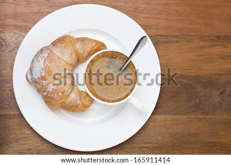 fresh croissant and cup of coffee on a plate on wooden background, top view, close-up - stock photo