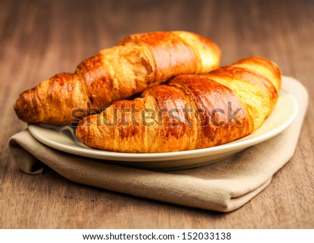 Fresh croissant on old wooden table - stock photo