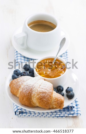 fresh croissant with orange jam, blueberries and coffee, vertical, top view