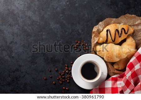 Fresh croissants and coffee on stone table. Top view with copy space - stock photo