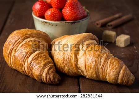 Fresh croissants on wooden table and bowl of strawberries, close up - stock photo