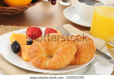 Fresh croissants with cantaloupe and berries - stock photo