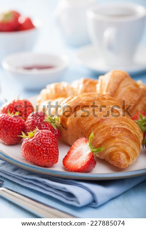 fresh croissants with jam and strawberry for breakfast - stock photo