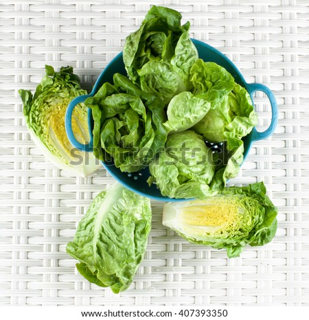Fresh Crunchy Romaine Lettuce Full Head and Halves in Blue Colander closeup on Wicker background. Top View - stock photo
