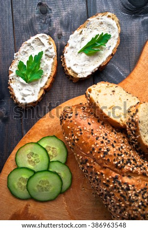 Fresh cucumber and baguette on beige cutting board and sandwich with cream cheese and parsley on rustic wooden background. Top view - stock photo