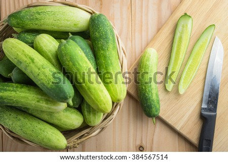 Fresh cucumber and slices on wooden table - stock photo