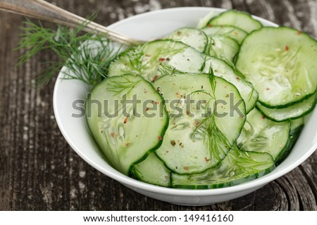 Fresh cucumber salad in bowl on wooden board - stock photo
