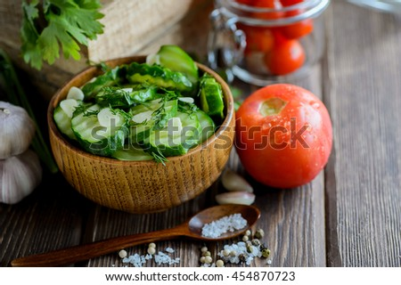 Fresh cucumber salad with fennel and garlic in bowl on wooden board