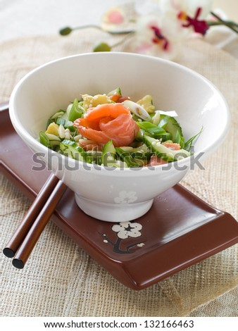 Fresh cucumber salad with salmon and sesame seeds, selective focus