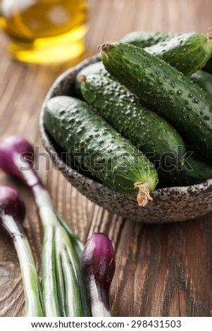 Fresh cucumbers in the bowl, green vegetables on wooden table