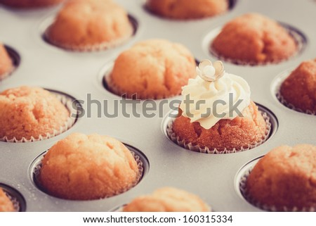 Fresh cupcakes in baking pan. Selective focus on cupcake with butter cream - stock photo