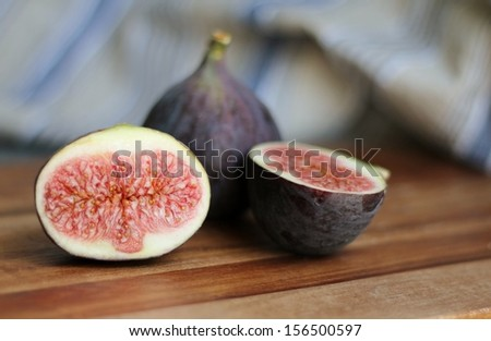 Fresh cut  figs on a wooden kitchen board, with blue striped linen in the background, shallow depth of field in domestic kitchen