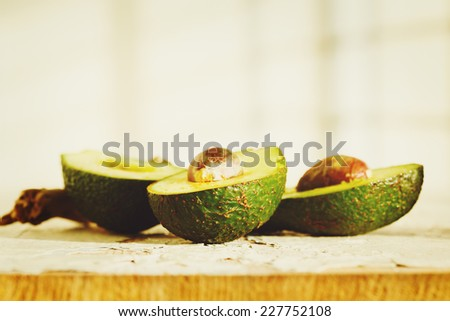 Fresh cut halves of avocado on wooden background. Image toned in warm green colors. - stock photo