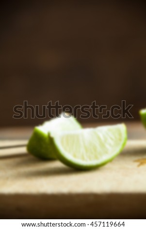 Fresh cut limes on wooden cutting board background with blur applied to image. - stock photo