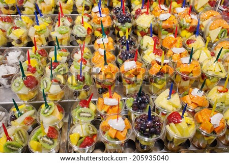 Fresh, cut, peeled mix of fruits of different kinds in containers with forks on a market stall, healthy diet nutritious street food, high vitamin content. - stock photo
