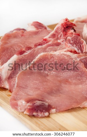 Fresh cut pork chops on wooden board.
