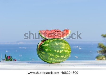 Fresh Cut watermelon on a wooden table in the garden.