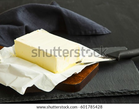 Fresh dairy butter piece on wooden cutting board