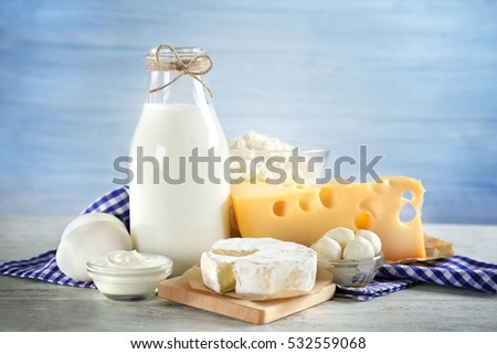 Fresh dairy products and napkin on table and light background