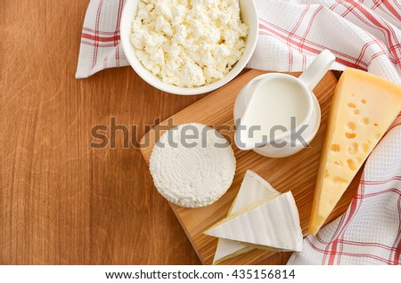 Fresh dairy products - milk, cheese, brie, camembert and cottage cheese on wooden background, top view, copy space. - stock photo