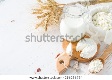 Fresh dairy products (milk, cottage cheese), wheat, white wood background, top view - stock photo