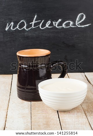 Fresh dairy products - milk, eggs. Rustic style. Bio/organic/natural ingredients. Healthy eating. Word natural on blackboard. - stock photo