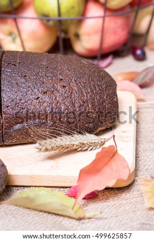 Fresh dark black - brown rye bread loaf, ears of grain, autumn colorful leaves, apples on jute table cover - tablecloth background.. Fresh, healthy whole grain bread. Closeup of sliced rye bread loaf