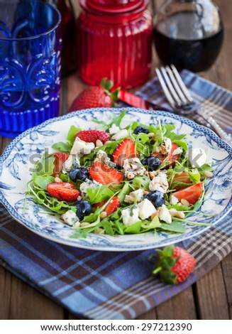 Fresh delicious arugula, strawberry, blueberry, pine nuts and blue cheese salad - stock photo